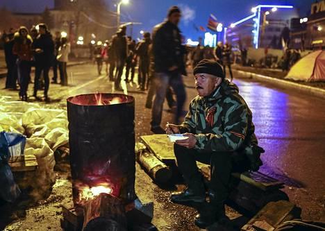 Venäjän-mielinen aktivisti söi illallista kadulla Luhanskissa, Itä-Ukrainassa, myöhään sunnuntai-iltana.