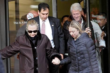 USA:n ex-ulkoministeri Hillary Clinton sairaalan ulko-ovella keskiviikkona tyttärensä Amyn ja aviomiehensä Billin (takana oikealla) seurassa.