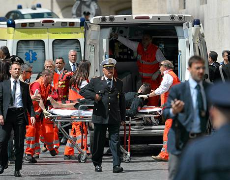 Toinen haavoittuneista poliiseista kannettiin ambulanssiin ampumavälikohtauspaikalla Rooman keskustassa.