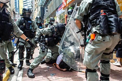 Mellakkapoliisit pitivät mielenosoittajia aisoissa Hongkongissa 1. heinäkuuta, kun Kiinan tiukka turvallisuuslaki oli astunut voimaan.