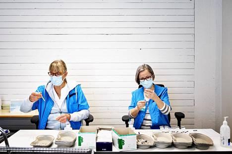 Mona Ansa, terveydenhoitaja (vas.) ja Marjo-Riitta Lintulaakso, anestesiahoitaja, laimentavat Pfizerin rokotetta Jätkäsaaressa Helsingissä.