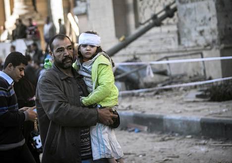Mies kantoi loukkaantunutta lasta autopommin iskettyä poliisiaseman lähellä Kairossa.