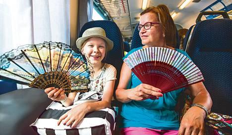 """E-juna, Pasila, 29,6 astetta. Iina Vahvaselkä ja Hannele Soivanen pitävät kesäisin aina viuhkoja mukanaan. """"Vanhassa junassa ilma ei käy ollenkaan, jos ei pääse istumaan ikkunan viereen"""", Soivanen kertoi Helsingissä maanantaina."""