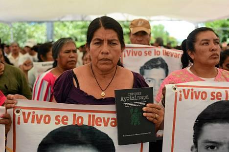 Kadonneen opiskelijan omainen osoitti mieltä Amerikan ihmisoikeuskomission raportti kädessään Meksikon Tixtlassa syyskuun alussa. Meksikon selvitystä 43 opiskelijan katoamisesta on arvosteltu puutteelliseksi.