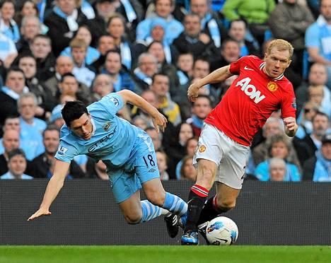 ManU:n Paul Scholes (oikealla) taistelee pallosta Manchester Cityn Gareth Barryn kanssa.