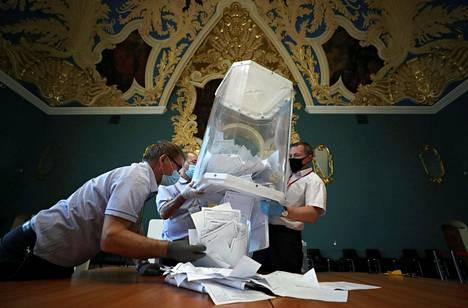Vaalilautakunnan jäsenet tyhjensivät vaaliuurnan äänestyksen päätyttyä äänestyspaikalla Moskovassa.