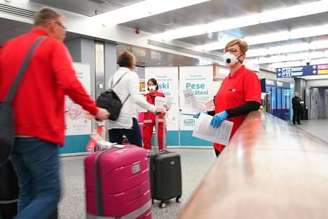 THL:n ja SPR:n työntekijät jakoivat tietoa koronakaranteenista Suomeen palaaville matkustajille Helsinki-Vantaan lentoasemalla keskiviikkona.
