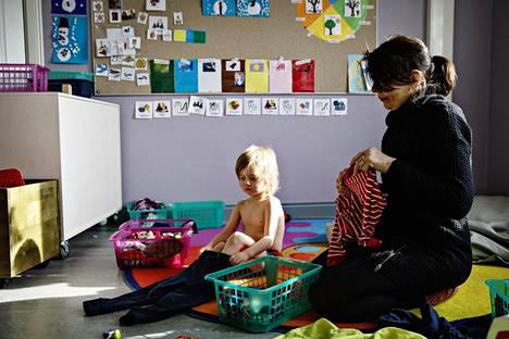 Lastentarhanopettaja Rita Haïdara auttoi kolmevuotiasta Peteriä pukemaan päiväunien jälkeen Linnunlaulun päiväkodissa Helsingissä. Haïdara tekee kokopäiväsen lastentarhanopettajan työn ohella toista työtä, jotta perhe pärjäisi.