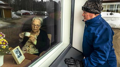 Yli 65 vuotta kestänyttä liittoa ei koronaviruskaan heikennä. Ylitorniolaiset Toivo ja Kaarina Makslahti viettävät hääpäiväänsä ikkunan läpi.