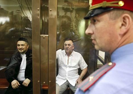 Toimittaja Anna Politkovskajan murhasta syytetyt Lom-Ali Gaitukayev (oik.) ja Rustam Makhmudov istuivat oikeussalin sellissä Moskovassa maanantaina.
