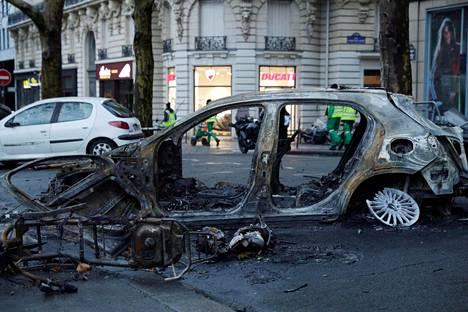 Mielenosoittajien polttama auto Pariisissa sunnuntaina.