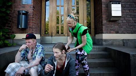 Kesän ajan Tampereella ympäristö- ja naapurustotyöntekijänä toimiva Karla Löfgren letittää Tampereen päihdepalveluyksikkö Breikin pihalla asiakkaan hiuksia. Miehet polttavat tupakkaa ennen korvaushoitolääkkeiden hakemista.