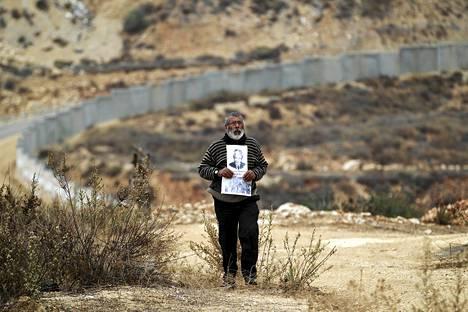 """Palestiinalaismies piteli edesmenneen vapaustaistelija Nelson Mandelan kuvaa Bilinin kylässä Länsirannalla. Taustalla näkyy Bilinin kylän jakava, Israelin pystyttämä muuri.  Palestiinassa pidetään Mandelaa suuressa arvossa. Palestiinalaishallinnon presidentti Mahmud Abbas muistutti perjantaina Mandelan tuesta palestiinalaisille. """"Palestiinan kansa ei ikinä unohda hänen lausuntoaan, jonka mukaan Etelä-Afrikan vallankumous ei ole saavuttanut tavoitteitaan ennen kuin palestiinalaiset ovat vapaita"""", hän kirjoitti."""