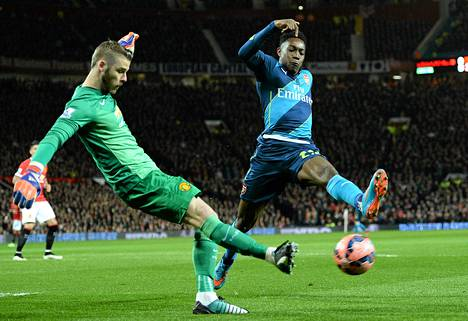 Manchester Unitedin maalivahti David de Gea (vas.) kamppailee pallosta Arsenalin Danny Welbeckin kanssa FA-cupin puolivälierässä maanantaina. Ottelu pelattiin ManU:n kotikentällä Old Traffordissa.