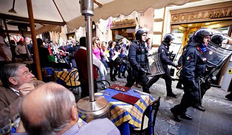 Turistit katselivat roomalaisessa kahvilassa mielenosoittajia saattelevaa mellakkapoliisien rivistöä keskiviikkona.