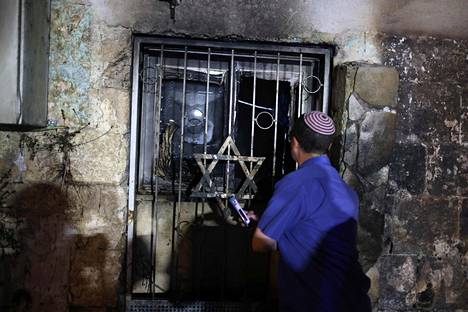 Juutalaismies katsoi sisään poltetun synagogan ikkunasta Lodissa perjantaina.