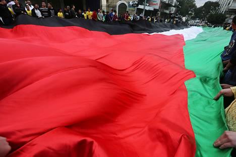 Palestiinalaiset kantoivat sata metriä pitkää Palestiinan lippua Jasser Arafatin kuoleman ja itsenäisyysjulistuksen vuosipäivän kunniaksi Nablusin kaupungissa Länsirannalla perjantaina.