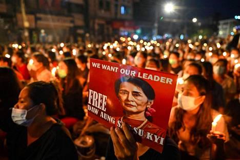 Mielenosoittaja piteli Aung San Suu Kyin kuvaa lauantaina Yangonissa kynttilätapahtumassa, joka muisti Myanmarin mielenosoituksissa kuolleita.