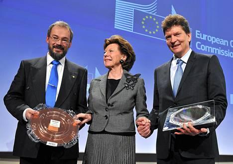 EU-komissaari Neelie Kroes onnittelemassa Göteborgissa sijaitsevan Chalmersin teknillisen korkeakoulun grafeenitutkijaa Jari Kinaretia (vasemmalla) ja The Human Brain Projectin johtajaa Henry Makramia.