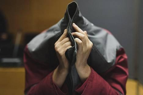 Syytetty piilotteli kasvojaan pusakan hupun alla.