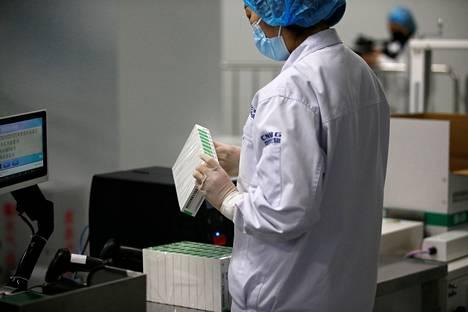 Työntekijä tarkasti rokotepakkauksia Sinopharm-lääkeyhtiön tiloissa Pekingissä helmikuussa.