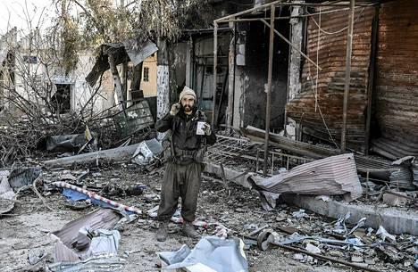 Kurditaistelija seisoo taistelujen raunioittamalla kadulla Kobanissa tiistaina.