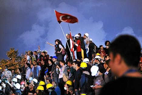 Hallitusta vastustavat mielenosoittajat levittivät Turkin lipun Gezi-puistossa sen jälkeen, kun Taksimin aukiolta oli siivottu levottomuuksien merkit: kyynelkaasukanisterit, barrikadit ja banderollit.