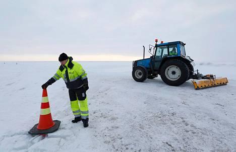 Pekka Virpi tasaa traktorin perälanalla jäätietä. Juha Toppi asettelee jäätien reunatolppia lähellä Hailuodon rantaa.