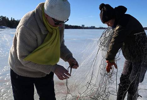 Helsinkiläiset Tiina Sandberg (vas.) ja Outi Setälä kalastamassa Laajalahdella maaliskuussa 2021. Verkoista löytyi talven aikana muun muassa kuoretta, kuhaa, siikaa, lahnoja ja hopearuutanoita.