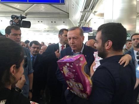 Turkin presidentti Recep Tayyip Erdogan jutteli Istanbulin lentokentän matkustajien kanssa lauantaina.