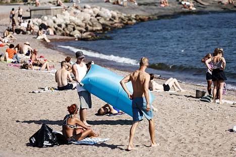 Ihmiset viettävät kuumaa kesäpäivää Eiranrannassa Helsingissä maanantaina.