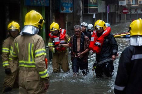Macaon saarella pelastustyöntekijät saattoivat tulvan saartamaksi joutunutta kauppiasta turvaan sunnuntaina.