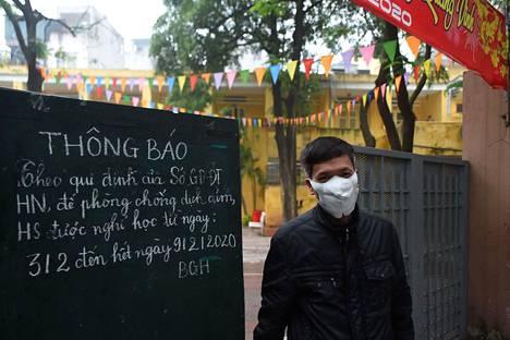 Vartija piti hengityssuojaa alakoulun portilla helmikuun alussa Hanoissa Vietnamissa.