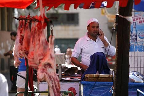 Uiguurimies lihanmyyntikojulla Urumqissa. Kuva vuodelta 2009.