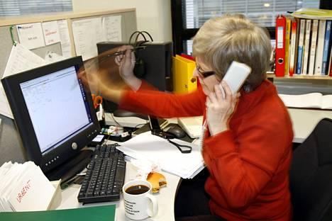 Kiireinen toimistotyöntekijä työpöytänsä ääressä.