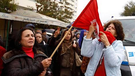 Nainen suuteli Tunisian lippua mielenosoituksessa pääkaupungissa Tunisissa torstaina.