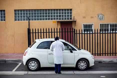 Terveydenhoidon työntekijä testaa auton matkustajia koronaviruksen varalta Johannesburgissa Etelä-Afrikassa.