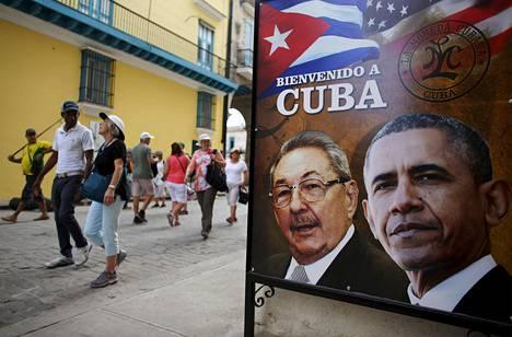 """Turistit ohittivat torstaina Havannan keskustassa Kuuban presidentti Raul Castron ja Yhdysvaltain presidentti Barack Obaman kuvin varustetun julisteen, jossa lukee """"Tervetuloa Kuubaan""""."""