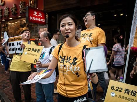 Demokratia-aktiivi jakoi esitteitä äänestyspaikan ulkopuolella Hongkongissa sunnuntaina.
