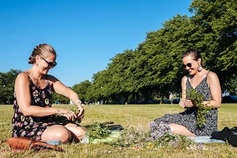 Essi Räsänen ja Anne Salmela tekivät seppeleitä Meripuistossa. Siitä alkaa muodostua jo vähitellen perinne, sillä kaksikon viime juhannus kului saman puuhan parissa.