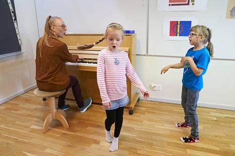 Opettaja Milla Pulska säestää Sophia Kiprianoffia ja Áile Kirste Lokkia (oik.), jotka innostuvat laulun lisäksi tanssimaankin.
