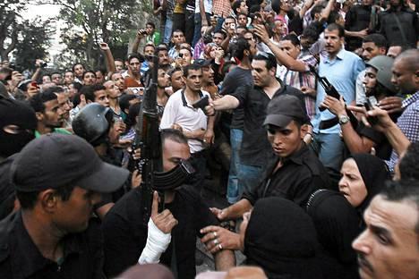 Uutistoimisto Reutersin mukaan siviilipukuinen poliisi osoitti aseella Mursin kannattajia, kun turvallisuusjoukot saattavat heitä ulos kairolaisesta moskeijasta lauantaina.