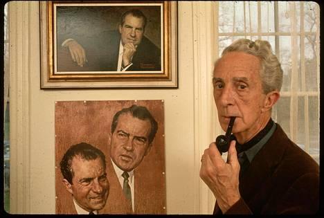 Taiteilija Norman Rockwell (1894–1978) polttaa piippua Norman Rockwell -museossa Massachusettsin Stockbridgessä. Taustalla muotokuva, jonka hän maalasi Richard Nixonista.