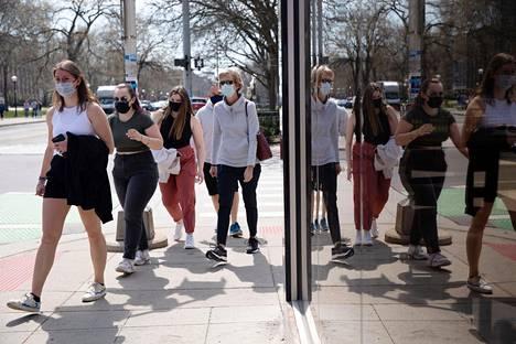 Kasvomaskeihin sonnustautuneet ihmiset menossa ravintolaan Michiganin Ann Arborissa 4. huhtikuuta.