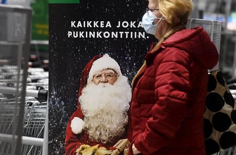 HS-gallupin perusteella enemmistö suomalaisista viettää joulua koronasta huolimatta samalla tavalla. Asiakas ohitti joulumainoksen kauppakeskus Triplassa Helsingissä marraskuussa.