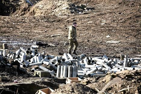 Separatistitaistelija etsi aseita Ukrainan armeijan tuhotun rakennuksen liepeiltä Debaltseven kaupungissa sunnuntaina.