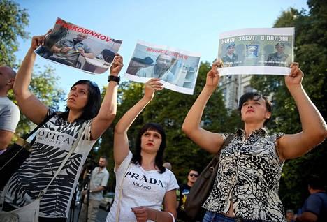 Ukrainalaisten sotavankien sukulaiset kantoivat läheistensä kuvia mielenosoituksessa Kiovassa maanantaina.