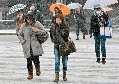 Jalankulkijat ylittivät tietä lumisateessa Tokiossa lauantaina.