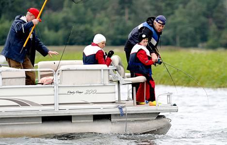 Kala on kiinni Tima Jarmolenkon, 9, uistimessa. Isä Pjotr ja äiti Sveta Jarmolenko jännittävät vieressä. Kalastusopas Erik Herlevi (vas.) haki esiin haavin.