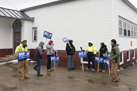 Joe Bidenia kannattavat sähkömiehet kampanjoivat äänestyspaikan ulkopuolella Penacookissa.